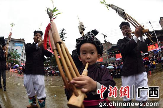 4月14日,在三江侗族自治县洋溪乡高露村中寨屯,一名小孩在吹芦笙。龚普康 摄