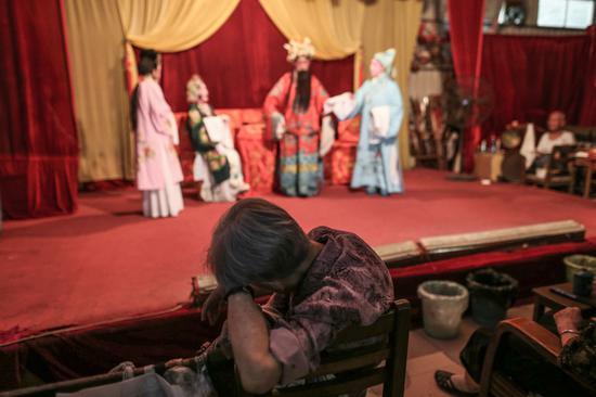△演出的过程中,一位老观众趴在椅子的靠背上休息。