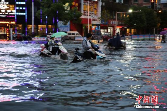 资料图:市民在雨中艰难出行。中新社发 魏东升 摄
