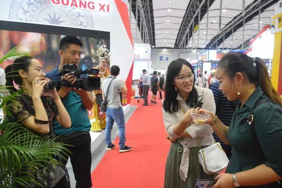 新闻媒体采访品尝油茶的观众