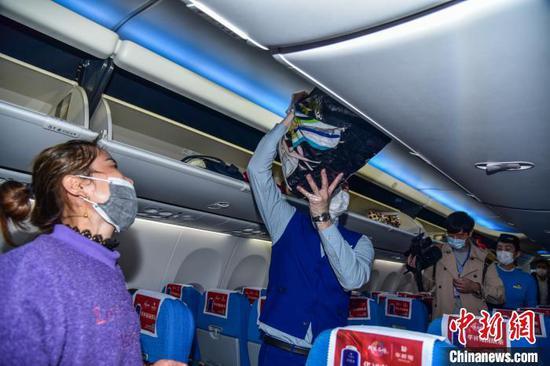 空乘人员帮助务工人员将行李放入行李架。 王以照 摄