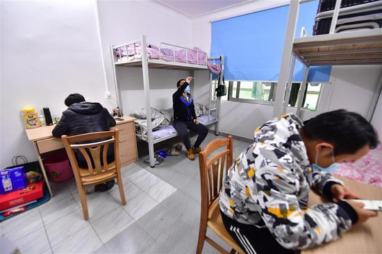广西桂林南溪山医院救护队司机温擎(中)在宿舍测量体温(2月7日摄)。 新华社记者 黄孝邦 摄