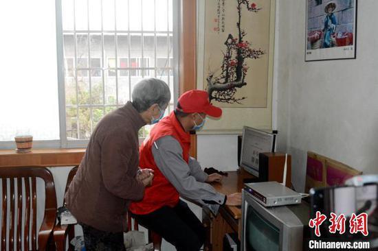 3月5日,志愿者上门为独居的老人修理电脑。 孙赟飞 摄