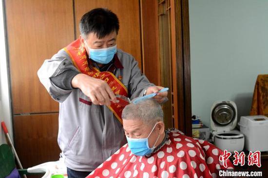 3月5日,柳州机车车辆有限公司志愿者王献忠为独居老人提供免费理发服务。 孙赟飞 摄