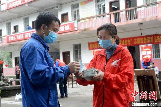 柳州机车车辆有限公司志愿者李建珍在学雷锋服务点为职工分发防控疫情服务手册。 孙赟飞 摄