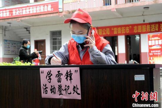"""3月5日,志愿者在""""雷锋街市""""服务点打电话联系预约登记的职工群众。 孙赟飞 摄"""