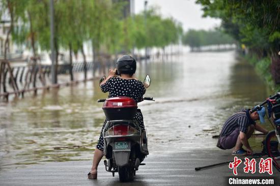 一位买菜路过的市民使用手机拍摄洪水景象。王以照 摄