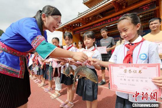 一名老师在给获奖学生发鱼。 龚普康 摄