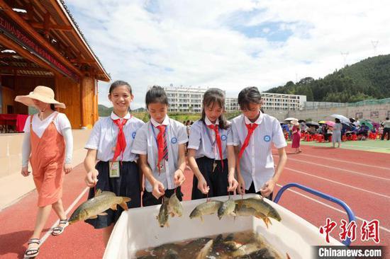 几名学生在协助老师发鱼。 龚普康 摄