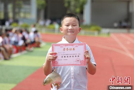 一名学生在展示自己的特殊奖品。 龚普康 摄