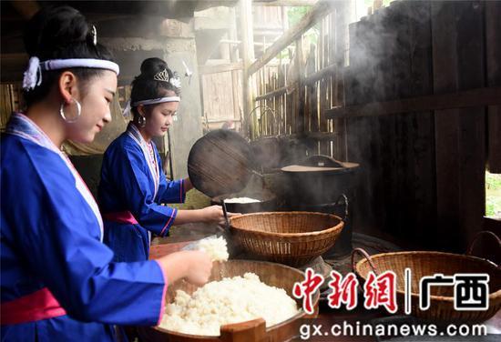 4月14日,在三江侗族自治县洋溪乡高露村中寨屯,两名姑娘在蒸糯米饭。龚普康 摄