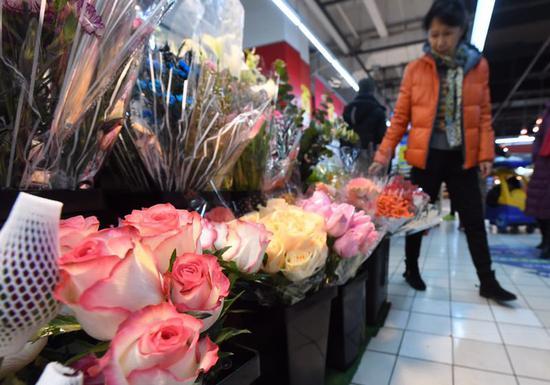 情人节前夕,消费者在超市内的鲜花摊位选购。新京报记者 吴宁 摄