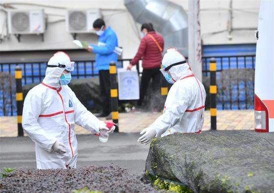 广西桂林南溪山医院救护队医生蒋结振(左)在给同事消毒(2月7日摄)。新华社记者 黄孝邦 摄