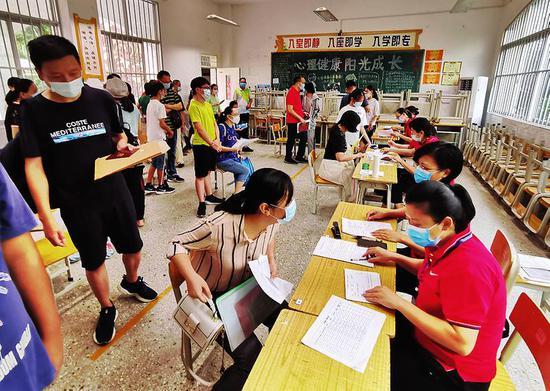 ▶今年7月,家长带着孩子办理初中新生入学报名手续。本报记者赖有光摄