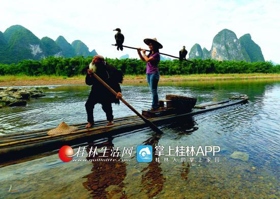 日前,游客在阳朔兴坪景区与漓江老渔翁黄全德合影。