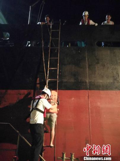 图为铺设软梯保护落水者过渡到海事趸船 朱建秋 摄