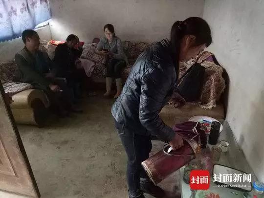 张贵华母亲潘英给过来探望的邻居倒茶水。