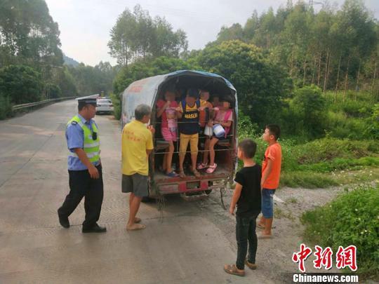 图为交警截停搭乘学生三轮车。 吴倩霞 摄