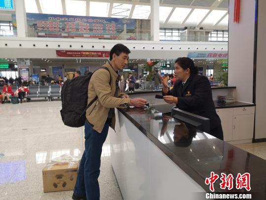 图为唐映梅给旅客解答疑问。 林馨 摄