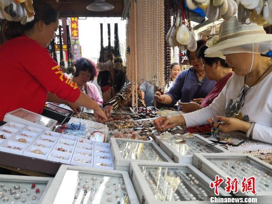 游客在北海市百年老街一家摊档前挑选珍珠饰品。 翟李强 摄