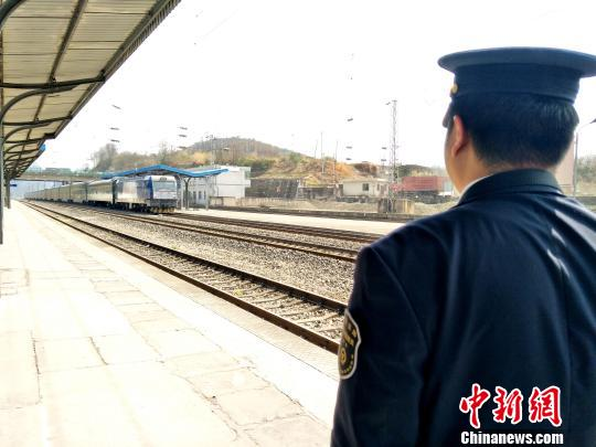 值班员刘鉴正在立岗接通过的客车。 王文龙 摄