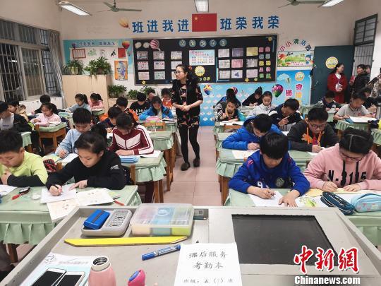 学生放学后在校内写作业,一名教师在值班。 朱柳融 摄