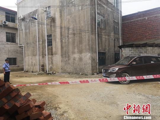 图为柳州市黄岭村汶村的案发现场,院子停放有一辆汽车,房子周围拉起的警戒线,有多名警察在现场把守,警方在现场设置了数字标记。 朱柳融 摄