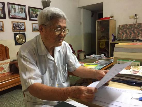 李庆符老人在家中写回忆录。