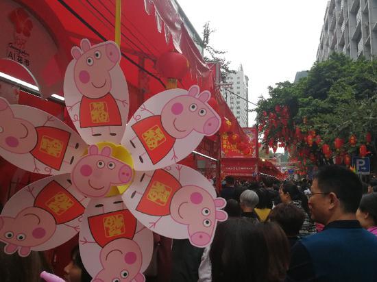 广州越秀花市上,逛花街的人们拿着小猪佩奇造型的风车。新华社记者徐弘毅摄