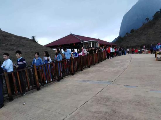 游客在天龙顶山地公园内排队乘车登山。