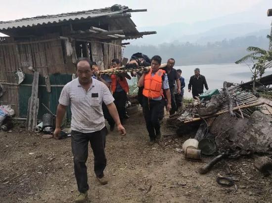 何永云(左一)和当地救援人员把落水者从江边转移到公路边
