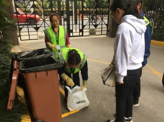 ▲ 在楼下帮忙垃圾分类的志愿者