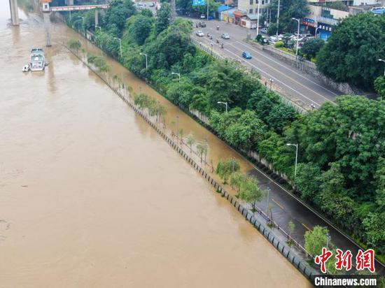 沿河道路被洪水淹没。 王以照 摄