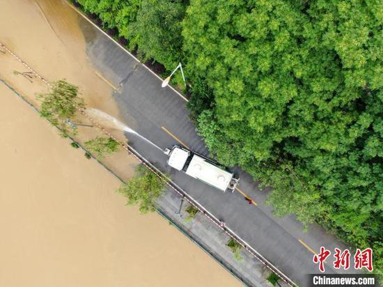 一辆洒水车清理退去洪水留来的淤泥。 王以照 摄