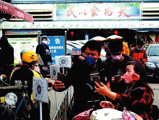 仙葫农贸市场门口设置了许多二维码供市民扫码出入