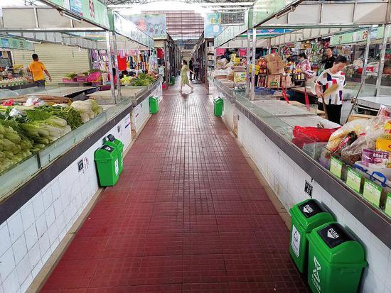 在高峰农贸市场,每个摊位前都摆放有分类垃圾桶。 南宁日报记者阮晓莹摄