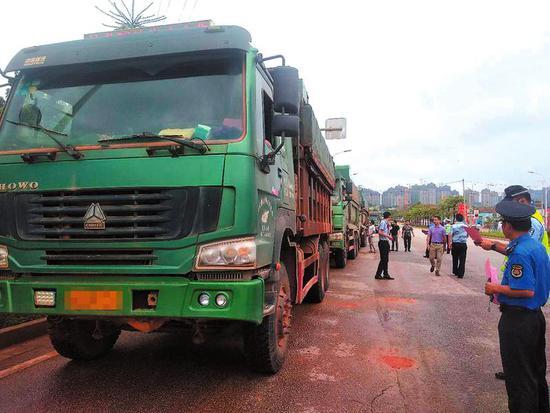 ▲执法人员对过往的泥头车进行检查 本报记者黎兆齐摄