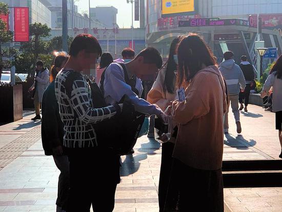 在朝阳广场,两名自称在实习的大学生(左一左二)正对市民推销