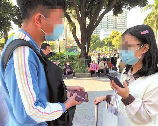 自称是正在实习的大学生拦下一名拉着行李箱的女孩推销笔本报见习记者陈来摄