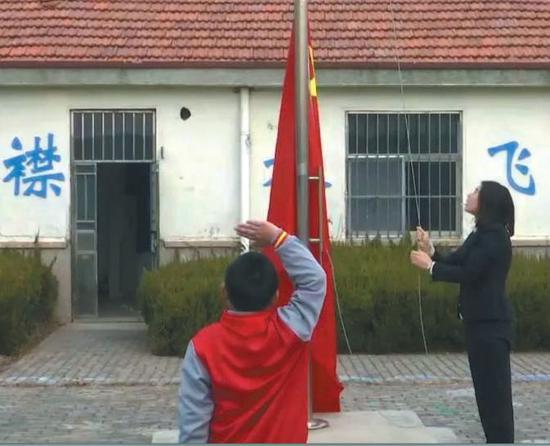 ▲竹岔岛小学,每周一,教师薛倩倩都会和9岁读二年级的学生薛文炫,一起升旗。受访者供图
