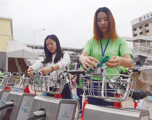 清洁好公共自行车后,志愿者在车把手系上绿丝带