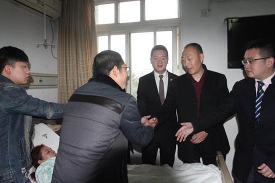 图二:杨女士家人激动的握住红瑞公司领导的手致谢