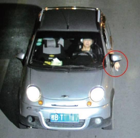 一名驾驶员在行车途中将手伸出窗外。