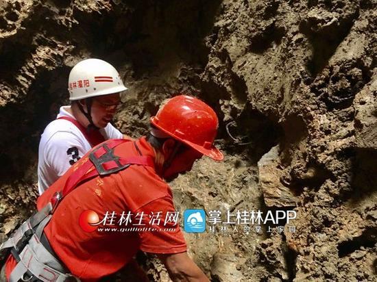 文物考古专家(白衣)在井内考察。记者高磊盈 摄