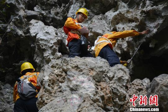 图为危石班职工站在岩石上测量危石。 林洁琪 摄