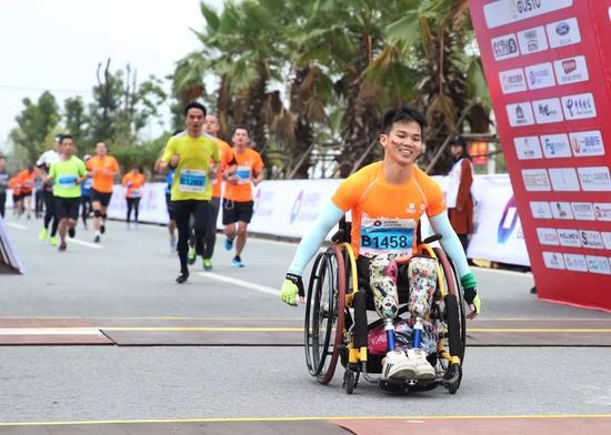一位坐在轮椅上的选手跑过终点。记者李凯 摄