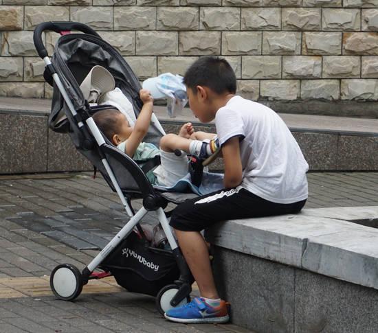 小哥哥看弟弟很有耐心,即使小脚踢到身上也不恼。笑槑/摄