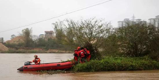 ↑消防员救援人员驾驶橡皮艇至孤岛下游位置