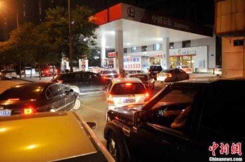 资料图:山西太原一加油站内,私家车主排队加油。中新社发 韦亮 摄