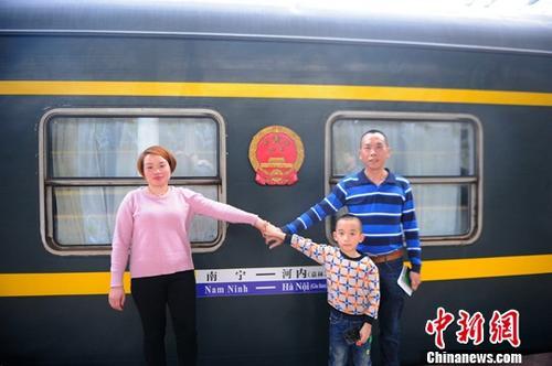 图为2月2日,梁氏娟一家三口在列车旁合影。中新社记者 蒋雪林 摄